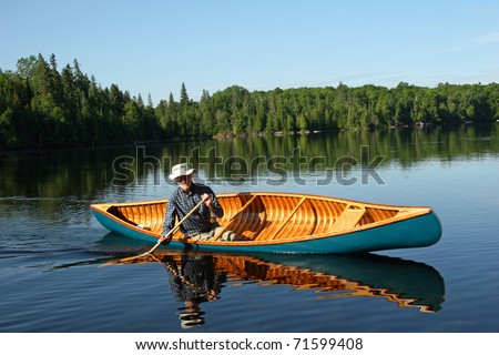 Canoeist paddling cedar canoe on a lake in northern Ontario, Canada