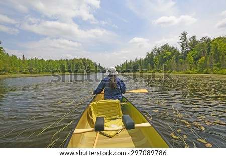 Canoer on a Crooked Lake in the Sylvania Wilderness in Northern Michigan - stock photo