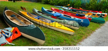 Canoes and Kayaks / Group of canoes and kayaks on a green grass - stock photo