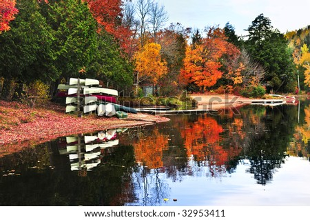 Canoes at forest of colorful autumn trees reflecting in calm lake - stock photo