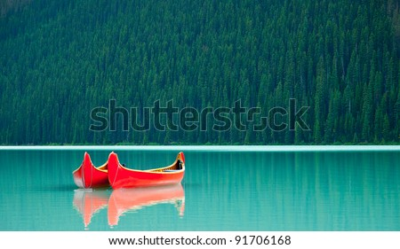 Canoes floating peacefully on the waters of Lake Louise, Banff National Park, Alberta, Canada. - stock photo