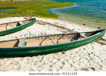 Canoes on the beach on a sunny day - stock photo