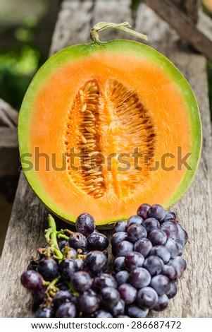 cantaloupe melon and Black grapes - stock photo
