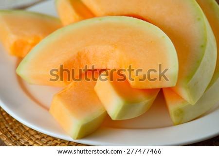 cantaloupe melon slices  on white plate - stock photo