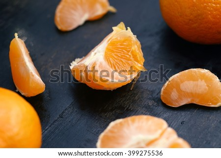 Cantels of mandarins with peels on a dark wooden table. Macro - stock photo