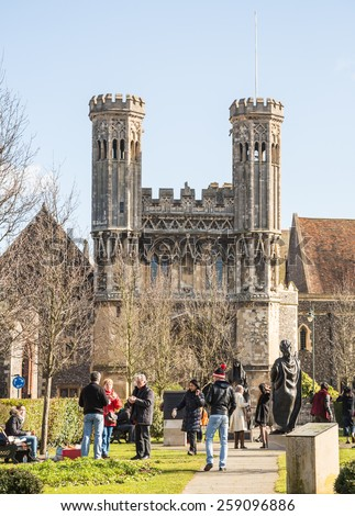 CANTERBURY, UK - FEB 27, 2015:  Tourists gather on Lady Wootton's Green, in front of St Augustine's gate, statues of King Ethelbert and Queen Bertha by Stephen Melton  were installed in 2007. - stock photo