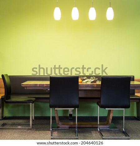 cantilever chairs at timber table with lamps and green wall - stock photo