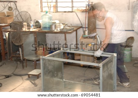 CANTON, CHINA - NOVEMBER 11: One of the biggest manufacturer of auto spray booths and generators in China. Worker weld aluminum frame on November 11, 2010 in Canton, China. - stock photo