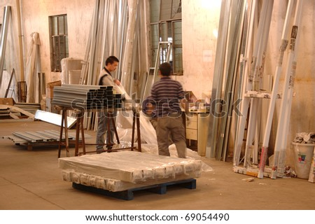 CANTON, CHINA - NOVEMBER 11: One of the biggest manufacturer of auto spray booths and generators in China. Workers unpack raw material for production on November 11, 2010 in Canton, China. - stock photo