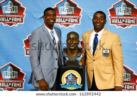 CANTON, OH-AUG 3: Duron Carter (L) and father and former receiver Cris Carter pose with his bust at the NFL Class of 2013 Enshrinement Ceremony at Fawcett Stadium on August 3, 2013 in Canton, Ohio. - stock photo