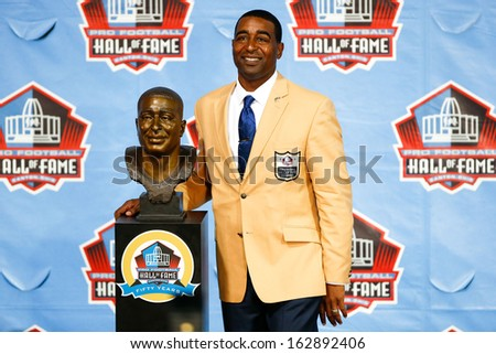 CANTON, OH-AUG 3: Former Minnesota Vikings receiver Cris Carter poses with his bust during the NFL Class of 2013 Enshrinement Ceremony at Fawcett Stadium on August 3, 2013 in Canton, Ohio. - stock photo