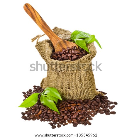 canvas bag with coffee beans decorated with green leaves and a wooden spoon isolated on white background