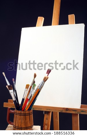 canvas, brushes and easel in black background  - stock photo