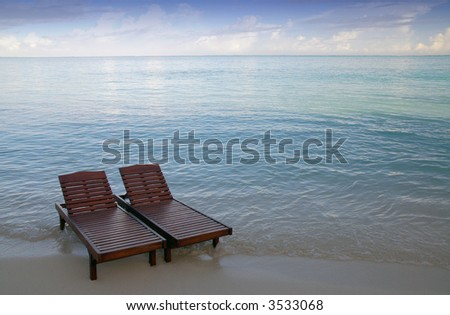 canvas chairs in the sea on a maldivian beach