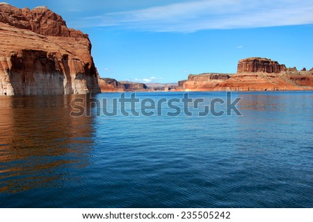 Canyon walls go on and on as you traverse Lake Powell.  Red sandstone cliffs line each side. - stock photo