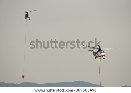 Canyonville, OR, USA - July 31, 2015: Type 2 helicopter comes in for a fill of its water bucket at a wildland fire in Oregon. - stock photo