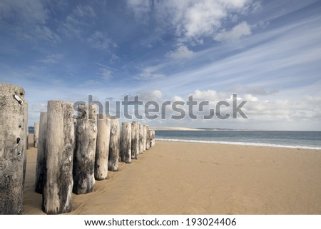 cap ferret beach with pyla sand dunes in the distance, france - stock photo