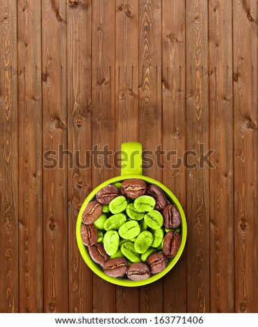 Cap with green and roasted coffee beans on wooden background. - stock photo