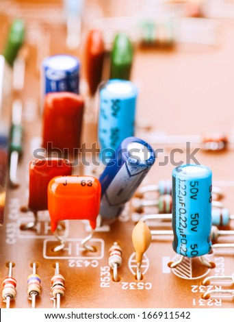 capacitors, resistors and other electronic components mounted on motherboard - stock photo