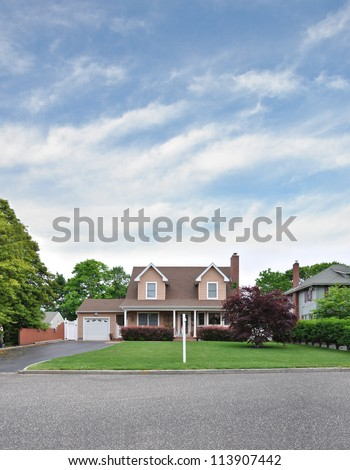 Cape Cod Style Home with For Sale Sign on Front Yard Lawn - stock photo