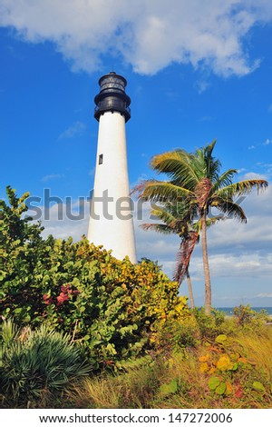 Cape Florida Light lighthouse with Atlantic Ocean and palm tree at beach in Miami with blue sky and cloud. - stock photo