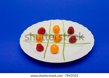 Cape gooseberries, raspberries and parsley arranged on a plate to look like a game of tic tac toe. - stock photo