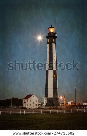 Cape Henry Lighthouse at dusk with a full moon lit in the background. This landmark lighthouse is one of the oldest in the USA. It was built of cast iron in 1879 on Fort Story in Virginia Beach. - stock photo