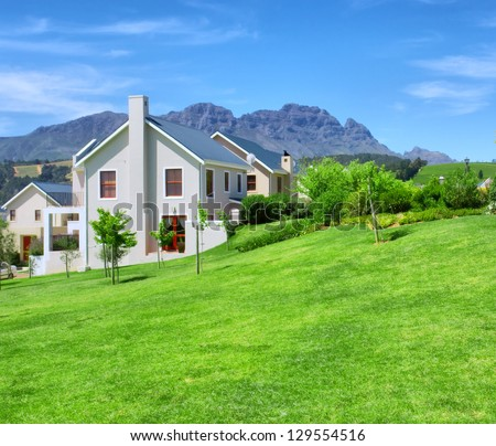 Cape-style house against blue misty mountains. Shot in Western Cape, South Africa. - stock photo