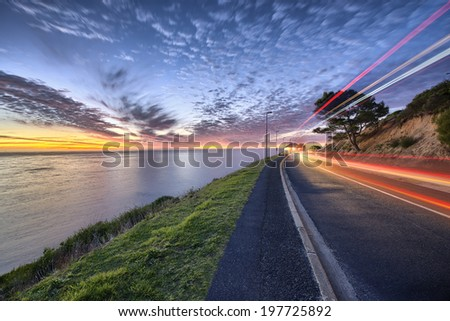 Cape Town sunset over ocean and road to the right with cars passing by shown with colorful streaks of light - stock photo