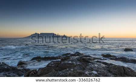 Cape Town Table Mountain's iconic flat top seen from Blouberg Strand in South Africa during sunset. - stock photo