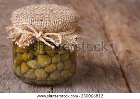 capers in a glass jar closeup on a wooden table. horizontal  - stock photo