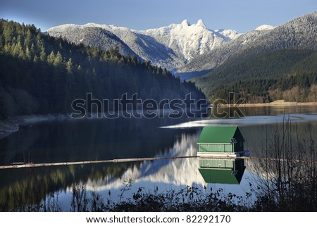 Capilano Reservoir Lake Green Building Dam Snowy Two Lions Snow Mountains Vancouver British Columbia Pacific Northwest - stock photo