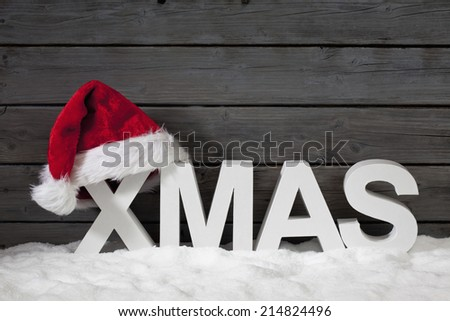 Capital letters forming the word xmas and christmas hat on pile of snow against wooden wall - stock photo