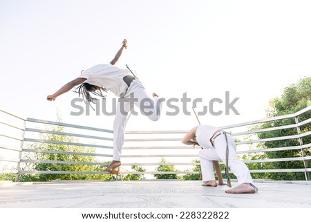 Capoeira, a woman and a man struggling in the outdoors - stock photo