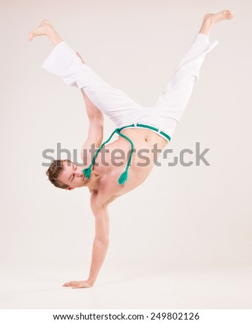 Capoeira, Man standing on one hand, white pants. - stock photo
