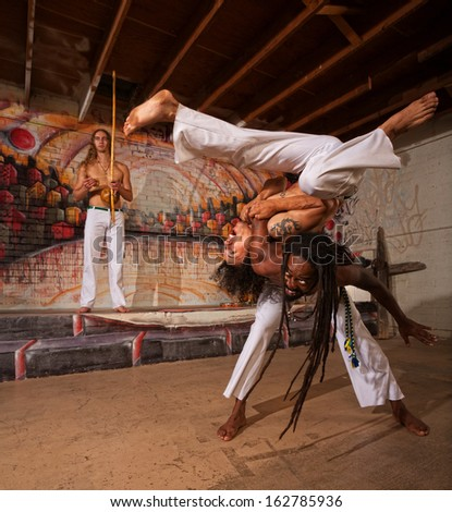 Capoeira man throwing partner over his shoulders - stock photo