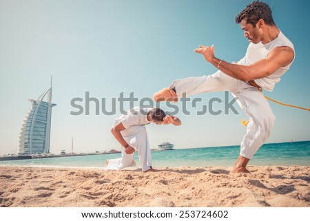 Capoeira team training on the beach - Martial arts athletes fighting - stock photo