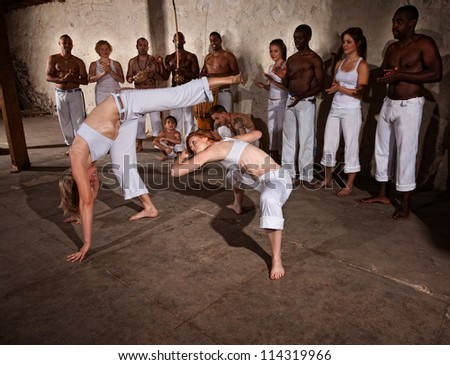Capoeria fighters kicking and dodging during a demonstration - stock photo