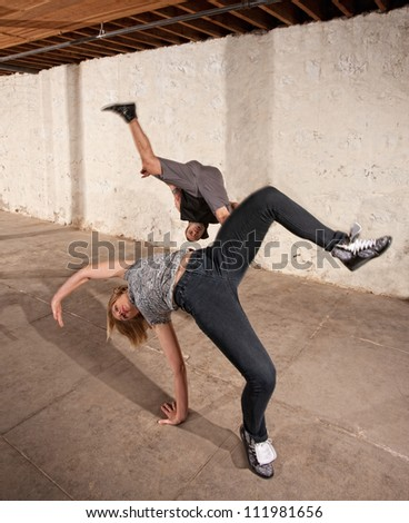 Capoeria martial artists performing aerial cartwheels - stock photo