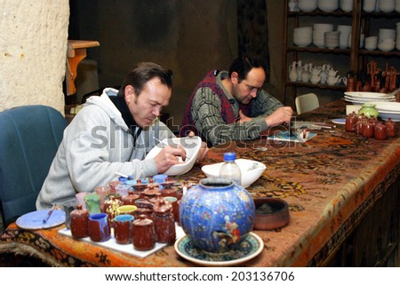 CAPPADOCIA, TURKEY - JANUARY 18: Ceramic artists drawing on traditional Turkish jug at Ceramic Workshop in Cappadocia on January 18, 2006 in Nevsehir, Turkey. - stock photo