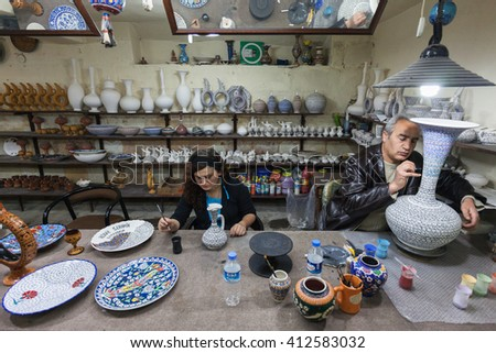 Cappadocia, Turkey - May 11, 2011: Inside his atelier, an unidentified artist and his apprentice works on a traditional ceramic vases.