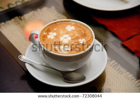 Cappuccino coffee at the table - stock photo
