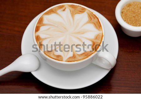 cappuccino, coffee cup and cane sugar on table - stock photo