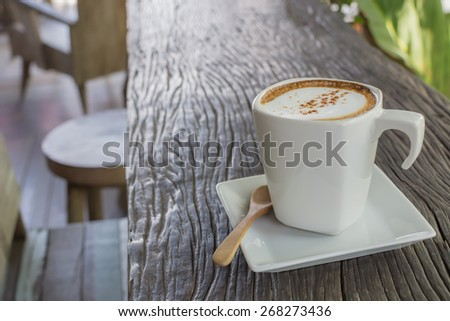 Cappuccino coffee cup on wood table - stock photo