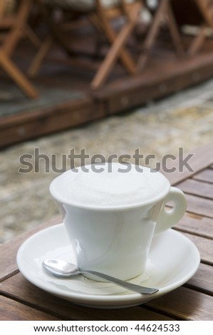 Cappuccino coffee cup outdoor in the street cafe over blur background - stock photo