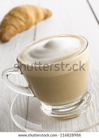 Cappuccino coffee cup with croissant on white table - stock photo
