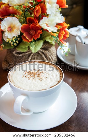 Cappuccino coffee cup with flower bouquet - stock photo