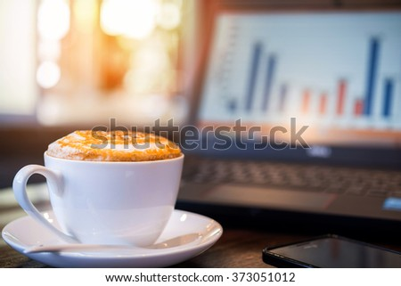 cappuccino coffee in red cup with graph on laptop, coffee shop background - stock photo