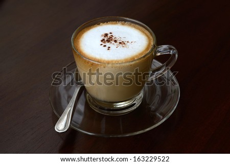 Cappuccino coffee served on wooden table.