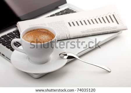 Cappuccino cup with laptop and newspaper - stock photo